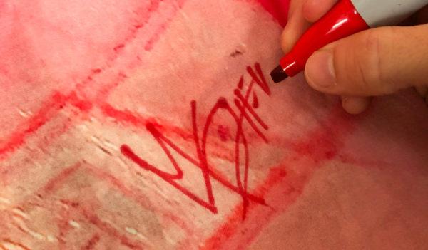 Marc Scheff signing his Venus v-neck v-dress limited edition garment