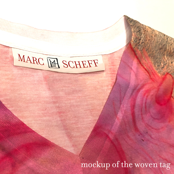 Mockup of the woven tag in the limited edition v-neck apparel from Marc Scheff